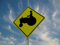 max tractor crossing street sign