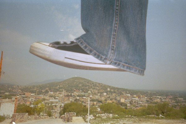 Giant shoe stepping on village