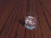 Glass with ice cubes on table