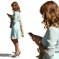woman wearing a blue dress standing and looking at her phone