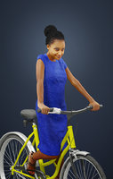 Macire An Elegant Black African Lady Dressed In An Ultramarine Blue Dress While Riding Her Yellow Bicycle