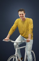 Vince A Caucasian Male Wearing A Yellow Sweater While Riding His Bicycle
